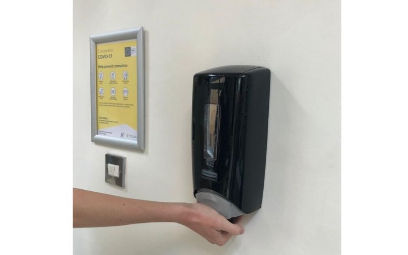 Sanitising hands with Underfoot Designs Covid-19 Hygiene Station